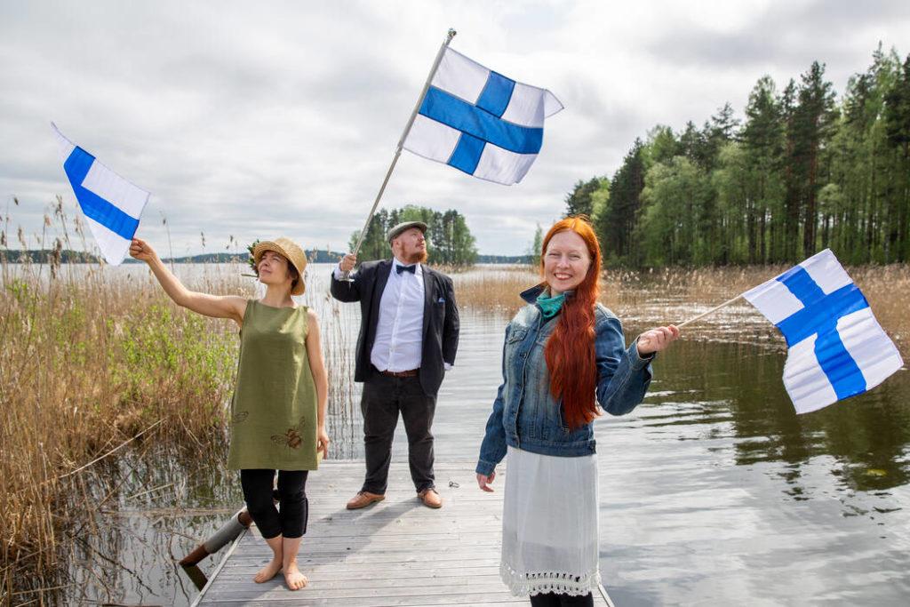 Kaksi naista ja mies heiluttavat Suomen lippuja laiturilla, taustalla näkyy järvi ja metsää.